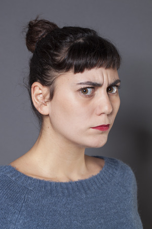 complain: doubt and worry concept - unhappy 20s woman with tied brown hair expressing suspicion or complain,gray background Stock Photo