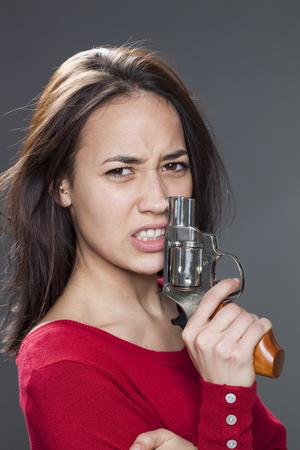 venganza: femenina concepto de energía - 20s infeliz niña multiétnico con el ceño fruncido en la celebración de un arma de venganza contra la agresión y la violencia