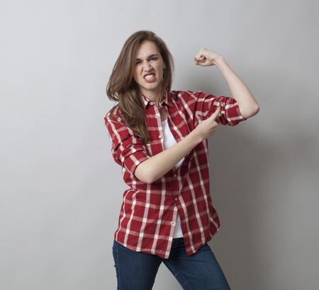 rolled up sleeves: girl power concept - aggressive beautiful young brunette showing her muscles with rolled up sleeves for feminine freedom,studio shot