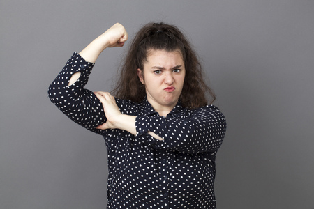 butch: girl power concept - pouting big young brunette showing her muscular arm for feminine independence,studio shot