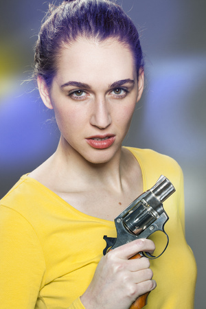 intimidating: female power concept - intimidating young woman with tied hair showing a handgun for impressing or expressing self-protection,retro light effects