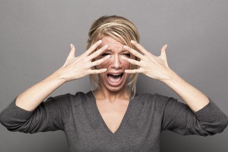 lacrime: Drama Queen concept - grida anni '20 ad alta voce ragazza bionda lamentarsi con le lacrime e le mani che nascondono il volto per lo spettacolo, sfondo grigio