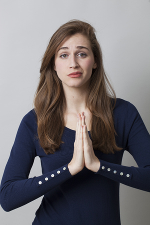 soothing: praying concept - unhappy beautiful 20s girl trying to pray or seek for zen position with soothing hand gesture, seeking for relaxation,studio shot Stock Photo