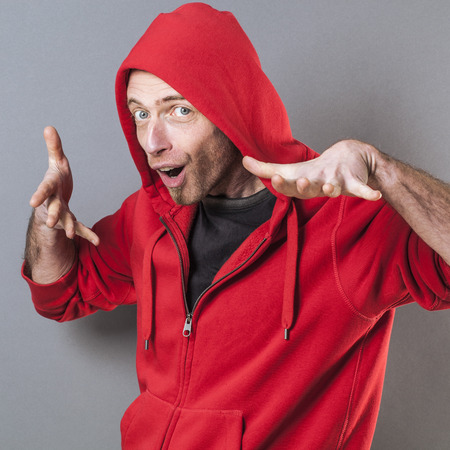 adolescencia: masculina concepto de la adolescencia - la edad media fresca que llevaba un su�ter con capucha rapero rojo que juega con la diversi�n gesto de la mano, estudio