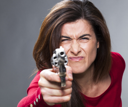 nearsighted: female power concept - near-sighted 30s brunette shooting with a handgun in foreground,training herself for self-defense or as a police officer,studio shot