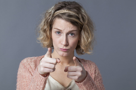 recognizing: doubt and worry concept - upset 20s woman with blond curly hair looking concerned recognizing or accusing someone with both fingers,grey background