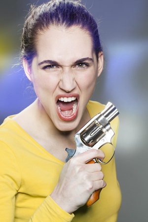 enraged: female power concept - enraged young woman shouting in holding a gun for revenge against aggression and violence,retro light effects