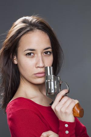 venganza: Concepto de la potencia femenina - chica multiétnica hermosa posando y mostrando un arma de venganza o la lucha contra el abuso