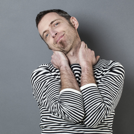 guy portrait: doubt and reflection concept - portrait of smiling 40s man looking satisfied with both hands holding his neck for relaxation,grey background