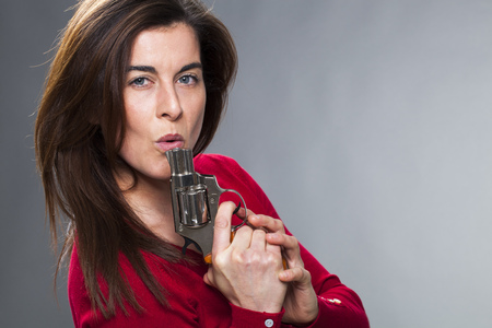chic woman: female power concept - sexy 30s brunette blowing onto her gun playing  Stock Photo