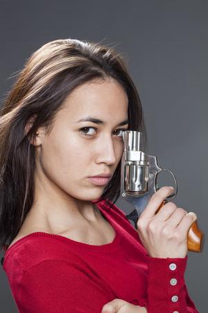 mujer con pistola: concepto de poder femenino - chica bonita multi�tnica que presenta y que muestra un rev�lver para su propia protecci�n o la lucha contra el abuso