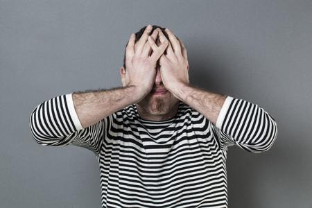 fout concept - verstoord middelbare leeftijd man met gestreepte trui verbergt zijn gezicht voor blindheid betreuren en teleurstelling Stockfoto