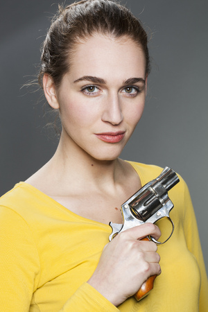 tied hair: female power concept - gorgeous young woman with tied hair showing a revolver for self-defense
