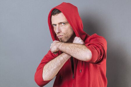 40s: male power concept - unhappy 40s man wearing an adolescent hoodie countering fight with both arms crossed,studio shot