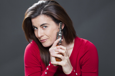 female power concept - happy gorgeous 30s brunette holding a gun,training herself as a dangerous businesswoman,studio shot
