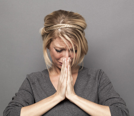 heartbroken: praying concept - heart-broken young blond woman holding her face down with hands praying together for better news,complaining and crying with disillusion