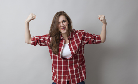 rolled up sleeves: girl power concept - laughing beautiful young brunette showing her muscles with rolled up sleeves for feminine freedom,studio shot
