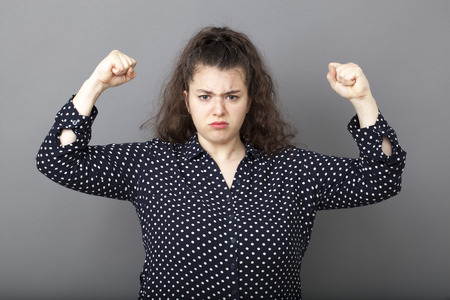manlike: girl power concept - unhappy overweight young brunette showing her muscular arm for feminine independence,studio shot