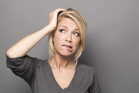 疑いし、心配コンセプト - 気になる 20 代かわいい金髪の女性、彼女の頭に触れる手と疑惑や不安を表現する灰色の背景