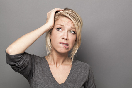 twijfel en zorgen concept - angstig 20s schattige blonde vrouw uiting van wantrouwen en angst met de hand aan te raken haar hoofd, grijze achtergrond Stockfoto