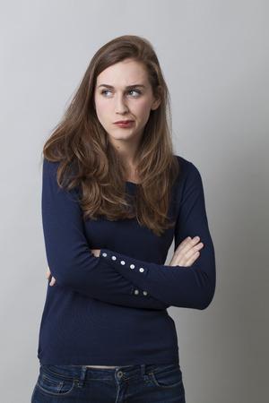 vrouwen: twijfel en zorgen concept - pruilen 20s vrouw met lang bruin haar afkeer met ontevreden lichaamstaal, studio-opname