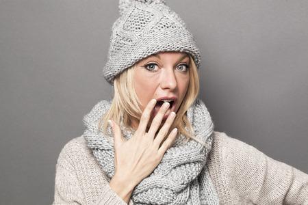 desilusion: Concepto de error - aturdido joven rubia señora llevaba ropa de invierno de moda que expresan sorpresa y decepción, estudio de fondo gris Foto de archivo