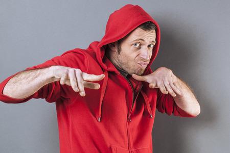 rapero: concepto de la adolescencia masculina - miedo media de edad llevaba un rapero su�ter con capucha roja de juego con gesto de mano de la diversi�n, estudio