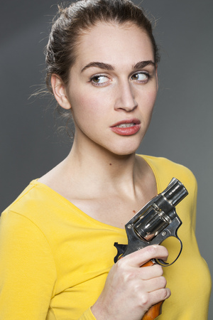 tied hair: female power concept - attractive young woman with tied hair holding a revolver for self-defense Stock Photo