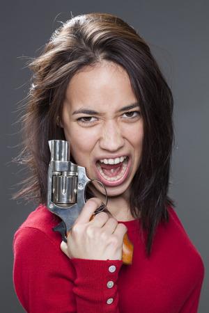 revenge: Concepto de la potencia femenina - 20s enfurecidos multi�tnica mujer gritando en la celebraci�n de un arma de fuego de venganza contra la agresi�n y la violencia