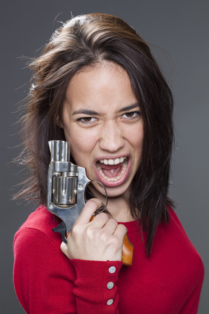 enraged: female power concept - enraged 20s multi-ethnic woman screaming in holding a handgun for revenge against aggression and violence