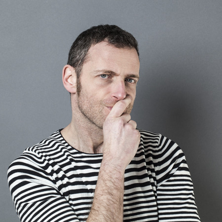 skeptical: doubt and reflection concept - portrait of unhappy 40s man looking skeptical with hand hiding his mouth for reflection,grey background