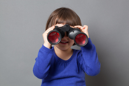 curiosity: kid exploration concept - smiling 4-year old child having fun in watching through binoculars for discovery and curiosity,studio shot