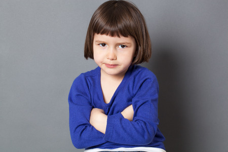 cute attitude: kid attitude concept - cute 4-year old child with bob cut making a statement in crossing arms for disagreement,studio shot Stock Photo