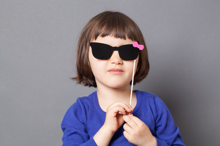 dressing up: fun kid glasses concept - girly preschool child holding fake black sunglasses for playing like her mother,dressing up as lady,studio shot
