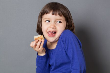 ni�o y ni�a: kid fun concept - thrilled preschool child eating a piece of bread,hiding herself for fun,enjoying silly childhood,studio shot