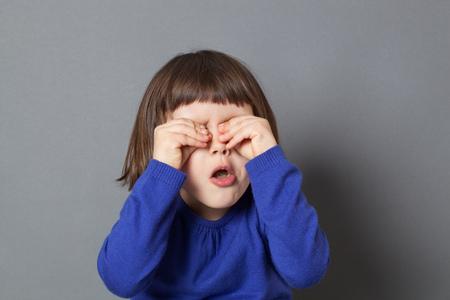 peekaboo: kid fun concept - cheeky preschool child playing peekaboo or hide and seek,rubbing eyes to be invisible for fun game,studio shot