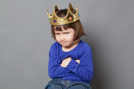 spoilt: spoiled kid concept - funny preschool child with golden crown on head folding arms for suspicious mollycoddled little king or queen metaphor,studio shot Stock Photo