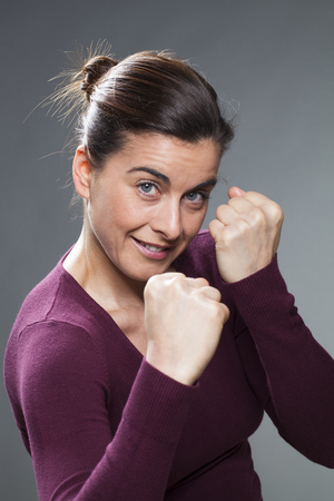 30s: female self-defense concept - attractive 30s woman smiling and confronting her athletic arms for fun confrontation or playful fight,studio shot