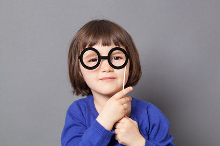 dressing up: fun kid glasses concept - wise preschool child holding fake black round eyeglasses for playing like adult or dressing up as smart nerd,studio shot