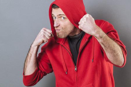 rapero: concepto de lucha masculina - rapero agresiva masculina de mediana edad que muestra los pu�os de provocaci�n o intimidaci�n actitud, tiro del estudio