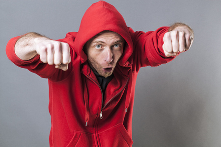conflicted: male fighting concept - funny middle age male rapper playing like a bad boy for intimidation with both fists in foreground,studio shot