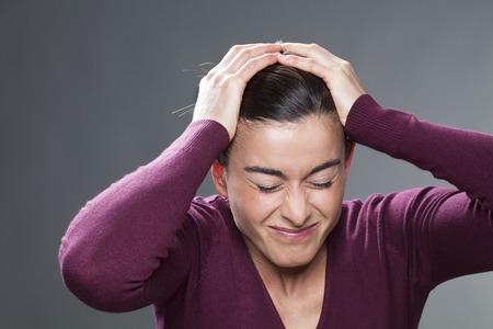 decepci�n: concepto decepci�n - 30s conmocionado mujer plegado ojos y se cubren la cabeza con las manos para pesar y confusi�n, tiro del estudio