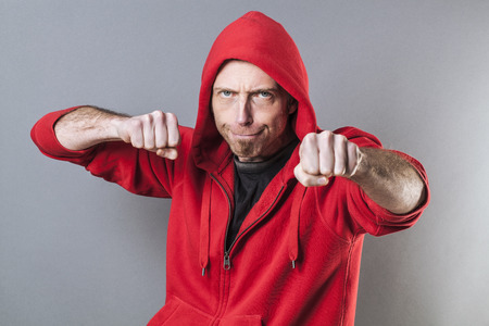 conflicted: male fighting concept - aggressive middle age male rapper playing like a bad boy for intimidation with his fists in foreground,studio shot