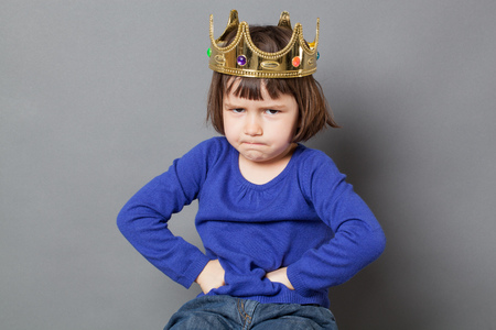 spoiled kid concept - sulking preschool child with golden crown on head putting hands on hips for confident mollycoddled little king or queen metaphor,studio shot