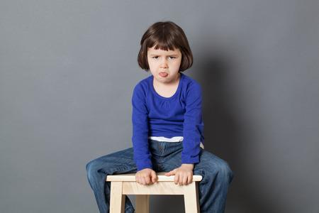 irrespeto: cabrito concepto de actitud - enfurruñado de 4 años de edad del niño que se sienta en la lengua se pegue taburete de madera para la arrogancia y el mal comportamiento, tiro del estudio Foto de archivo