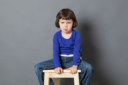 disrespect: kid attitude concept - sulking 4-year old child sitting on wooden stool sticking tongue for arrogance and bad behavior,studio shot
