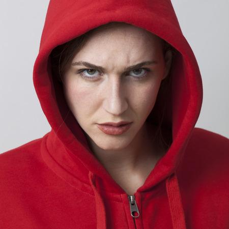 arrogancia: femenina concepto de amenaza - 20s enojado ni�a llevaba streetwear con sudadera con capucha expresar arrogancia adolescente, primer plano en el estudio Foto de archivo