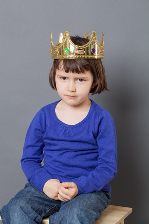 spoiled kid concept - sulking 4-year old child with golden crown on head sitting on wooden stool for little mollycoddled metaphor,studio shot Stock Photo