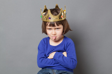 spoiled kid concept - cheeky preschool child with golden crown on head folding arms and sticking out tongue for disrespectful mollycoddled little king or queen metaphor,studio shot