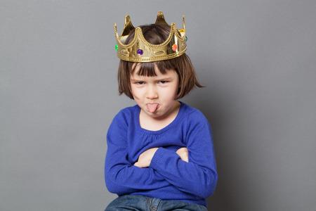 verwend kind concept - brutaal preschool kind met een gouden kroon op het hoofd vouwen armen en tong uitsteekt voor respectloos watten gelegd kleine koning of koningin metafoor, studio-opname